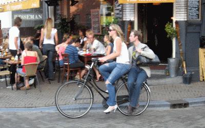 zwei Leute auf dem Fahrrad, eine Person auf dem Gepäckträger