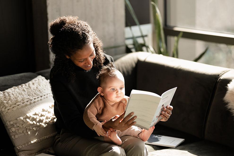 Moeder leest babydagboek met dochtertje