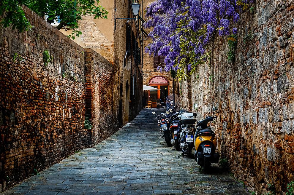 Scooters in een smal steegje in Siena, Italië