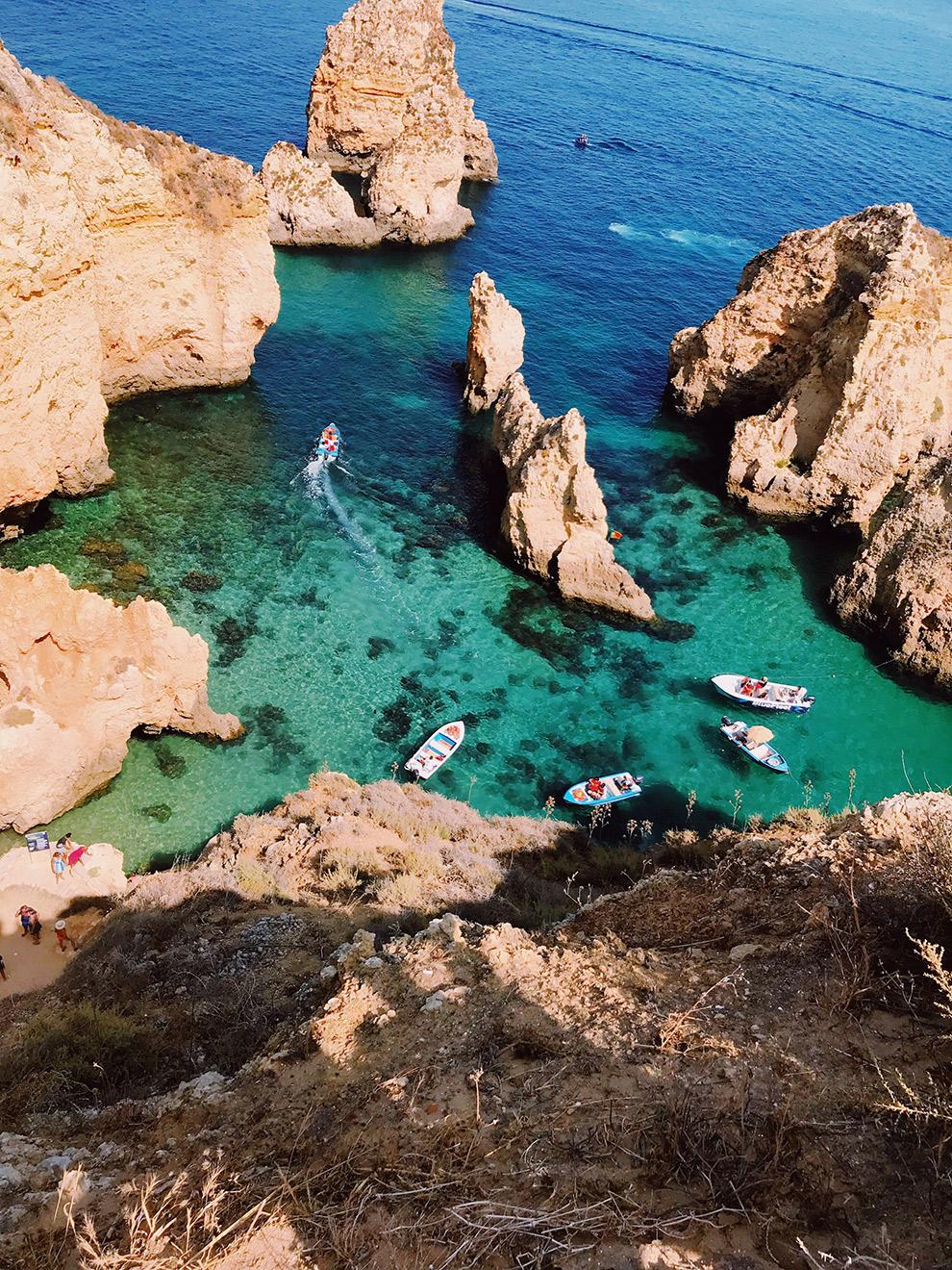 Helderblauw water tussen zandkleurige rotsformaties in de Algarve