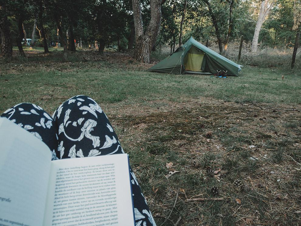 Boekje lezen naast de tent op camping in bos