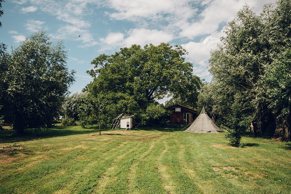 Grasveld met tipitent midden in de natuur