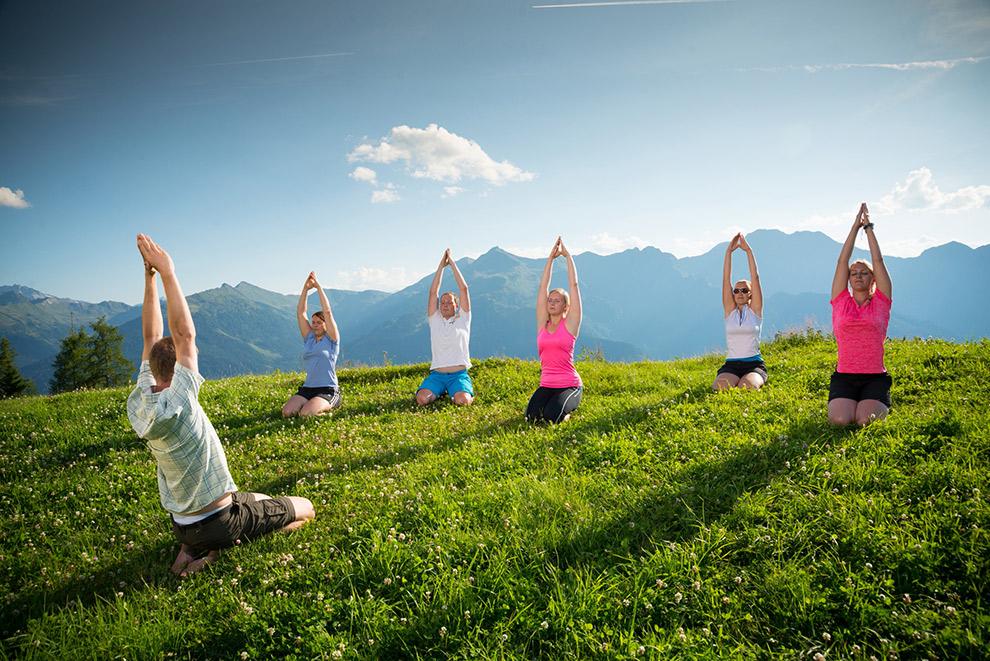 Yoga in het gras boven op berg in Grossarital, Oostenrijk