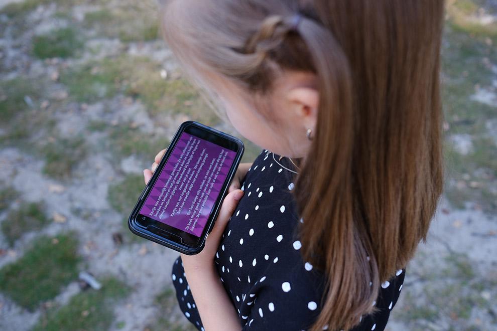 Nichtje nova houdt telefoon vast met daarop de sokkeltocht podcast