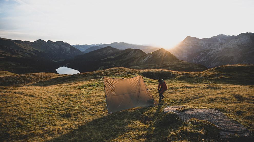 Tentje opzetten in de Alpen tijdens zonsondergang