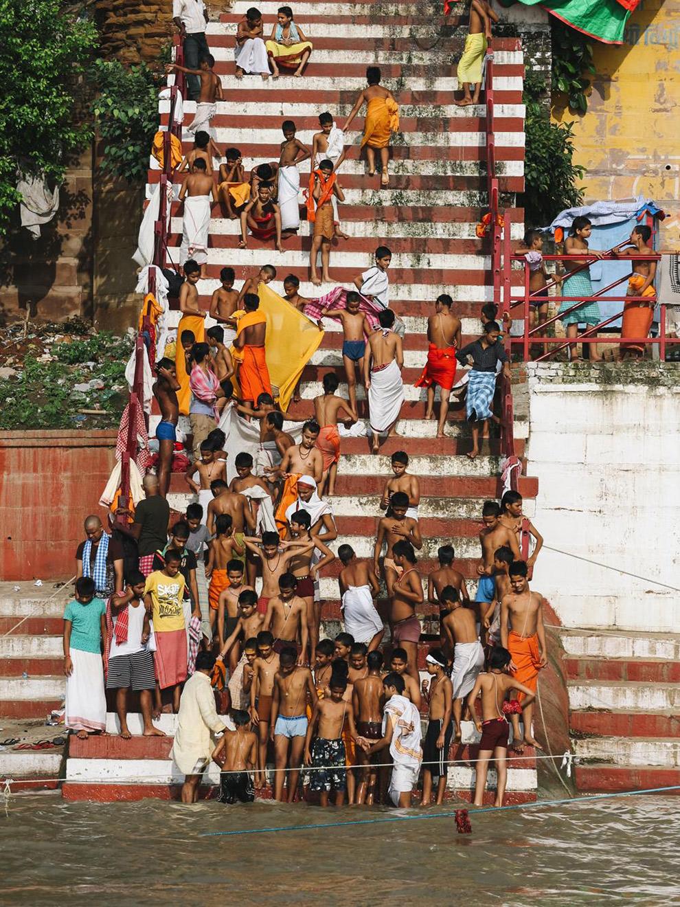 Kinderen verzamelen zich op trap om te wassen in de Ganges rivier in India