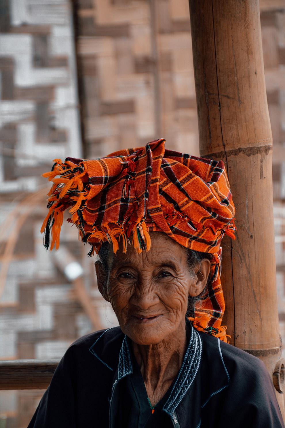 Portret van stralende vrouw in Myanmar met oranje doek