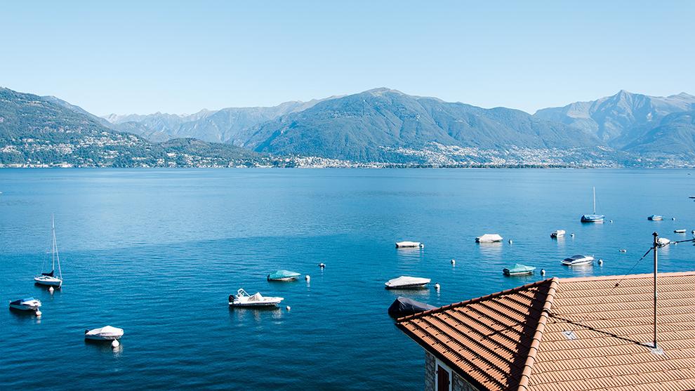 Bootjes drijven in het blauwe water van Lago Maggiore