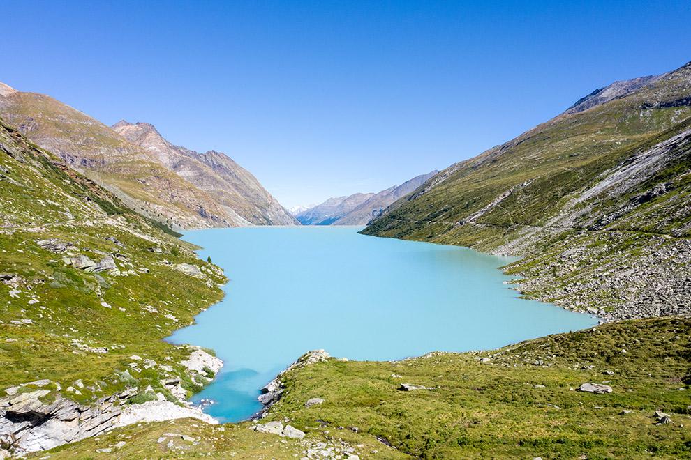Turquoise stuwmeer te midden van Zwitsers berglandschap