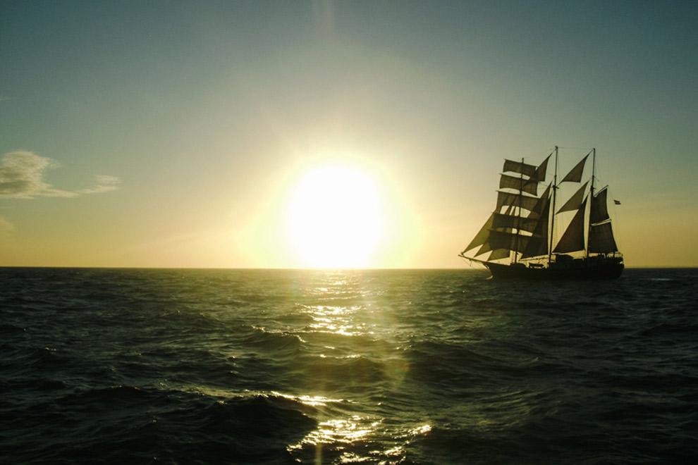Varen op zee met uitzicht over zeilboot en zon aan de horizon