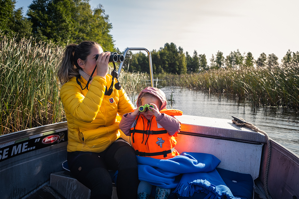 Moeder en dochter met verrekijker op het water