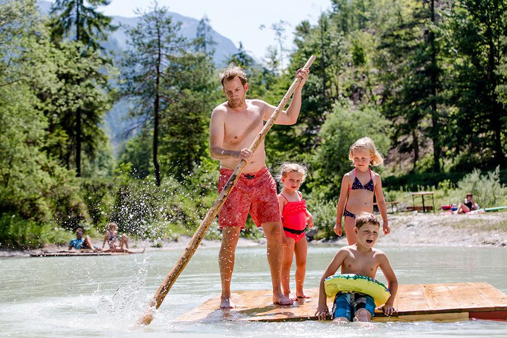 Familie beleefd plezier op het water op houten vlot in Oostenrijk