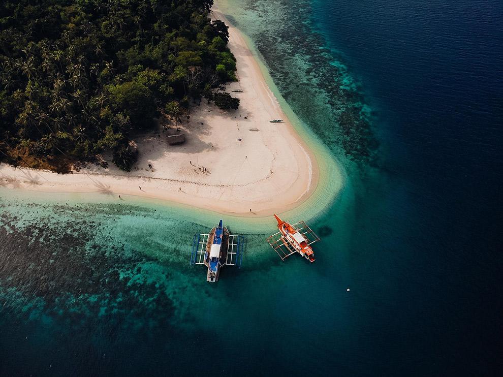 Dronefoto van strand in Filipijnen met lokale bootjes