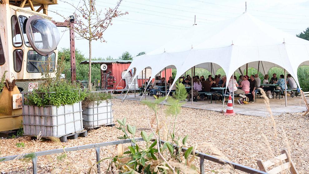 Terras met tent op een creatief industrieterrein aan het Almeerderstrand