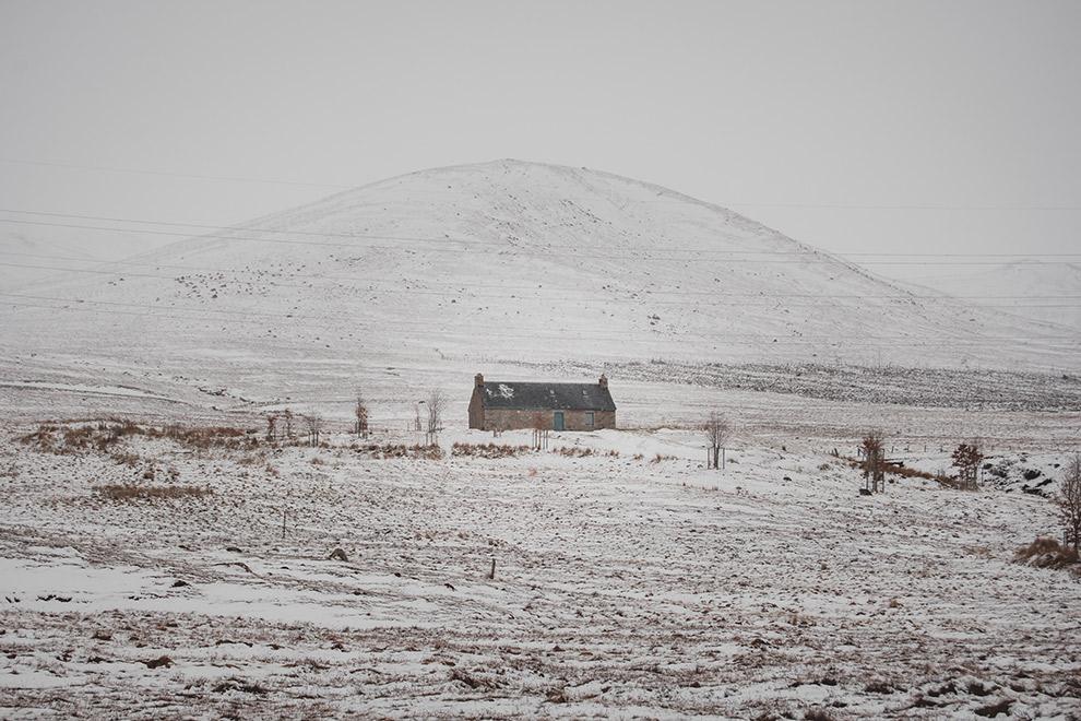 Rechthoekig huisje te midden een met sneeuw bedekt landschap