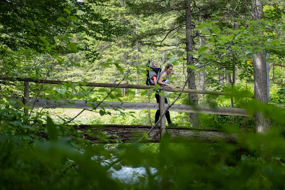 Moeder wandelt met een kinderdrager door de bossen