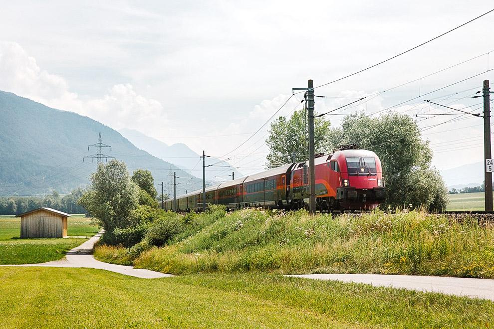 Rode trein raast door groen Oostenrijks landschap