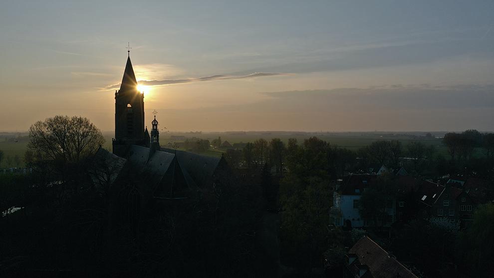Zon verdwijnt achter kerktoren in Monnickendam