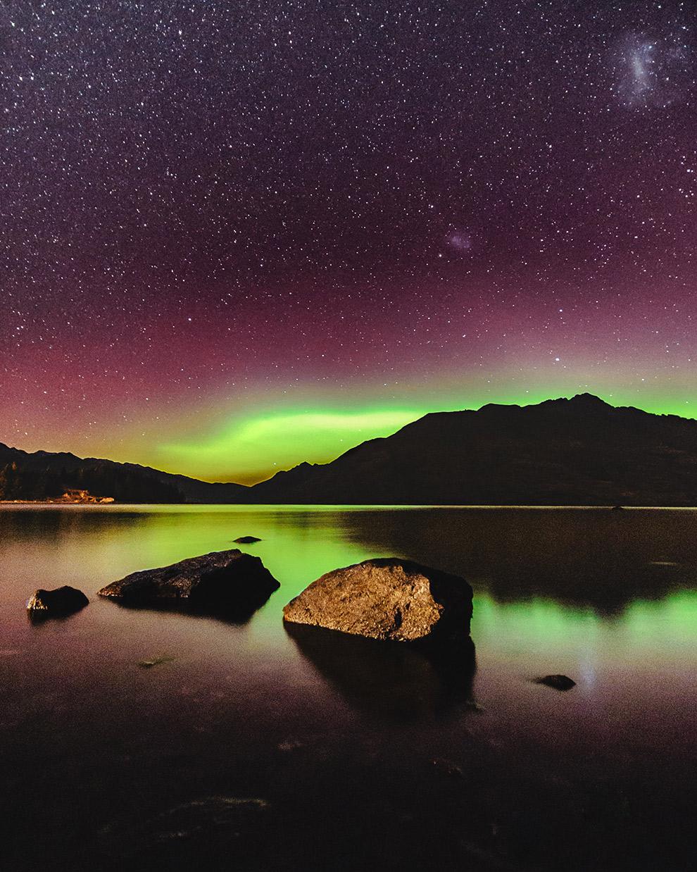 Paarse sterrenhemel met groen zuiderlicht dat in het water reflecteert