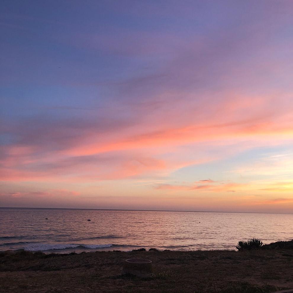 Suikerspin-kleurige zonsondergang op het strand in de Algarve