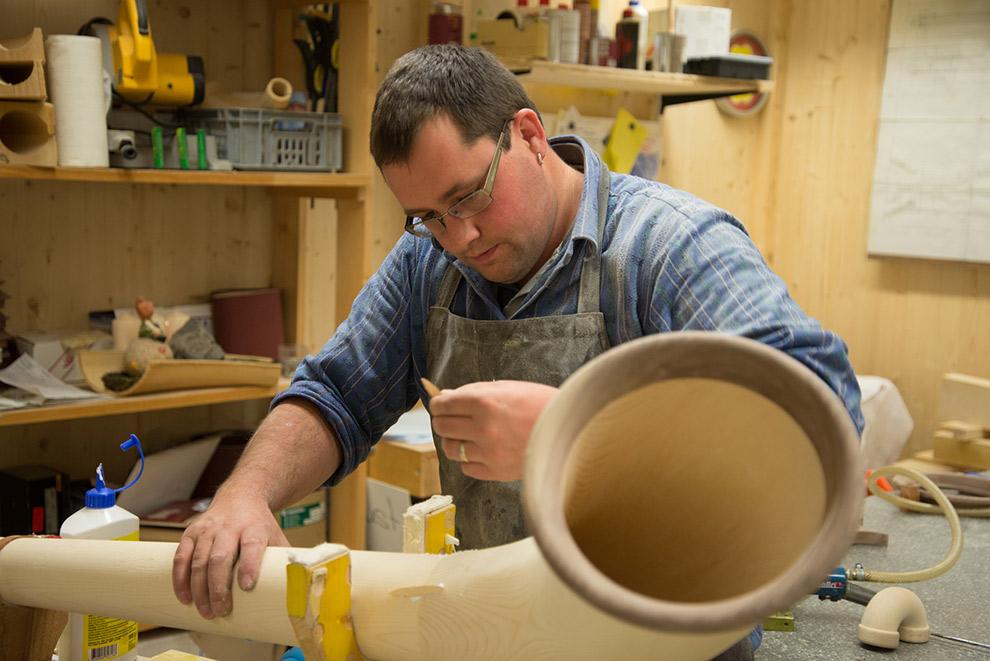Man werkt aan alpenhoorn in atelier