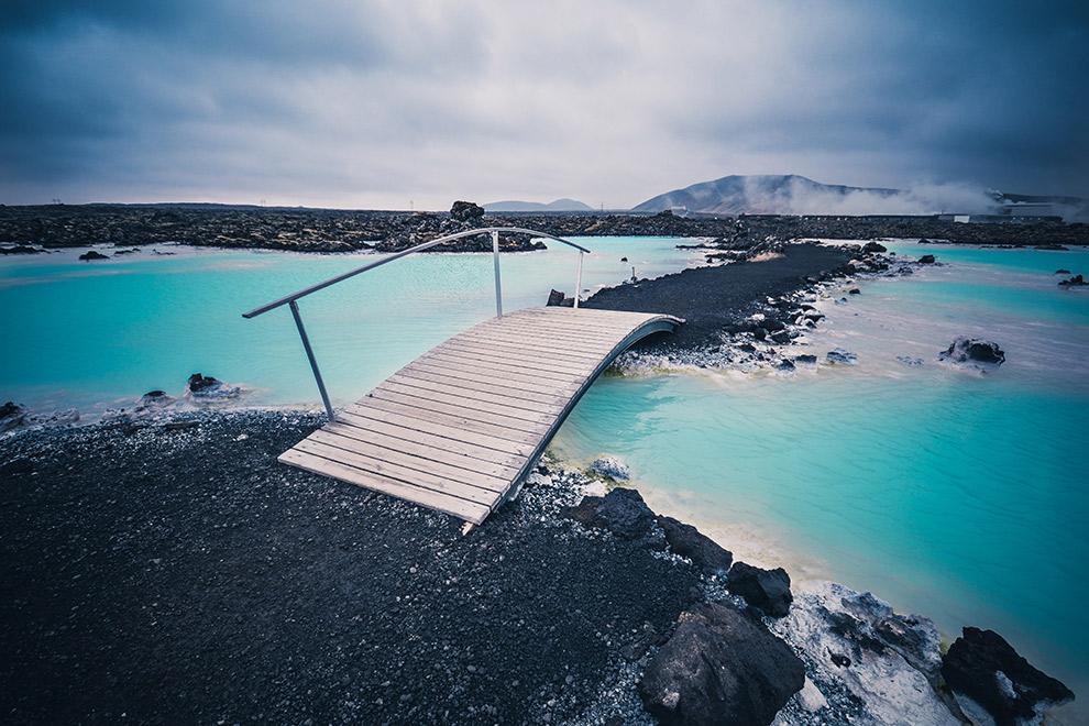 Brug over de blauw met zwart kleurende blue lagoon in IJsland