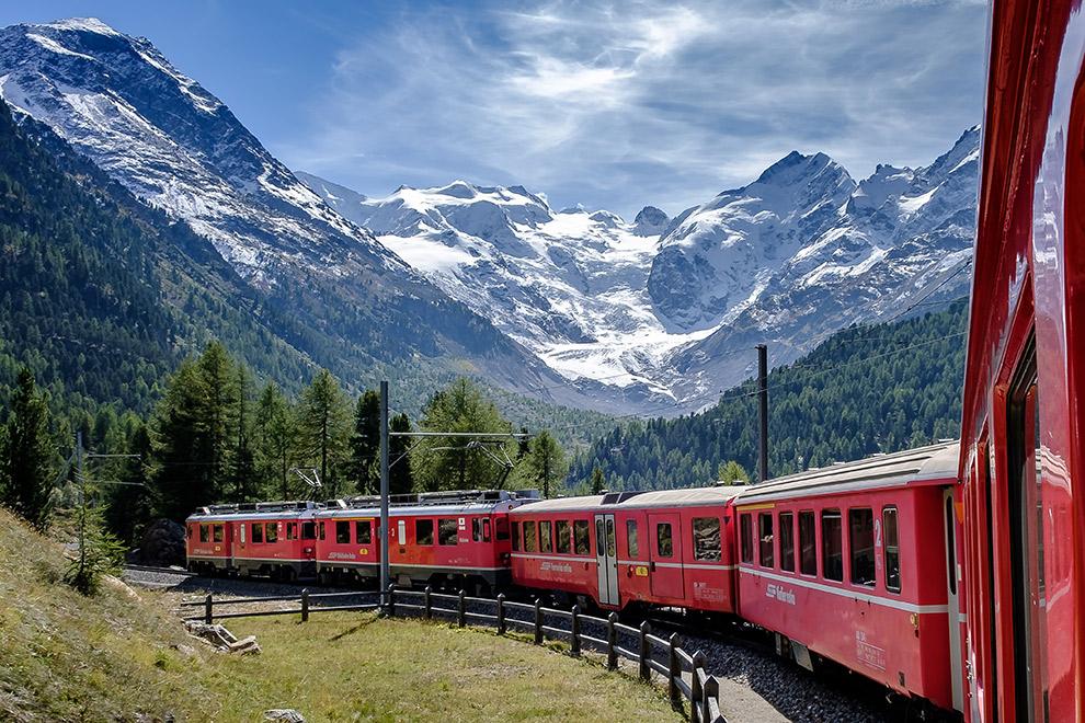 De rode Glacier Expers trein met op de achtergrond besneeuwde bergtoppen