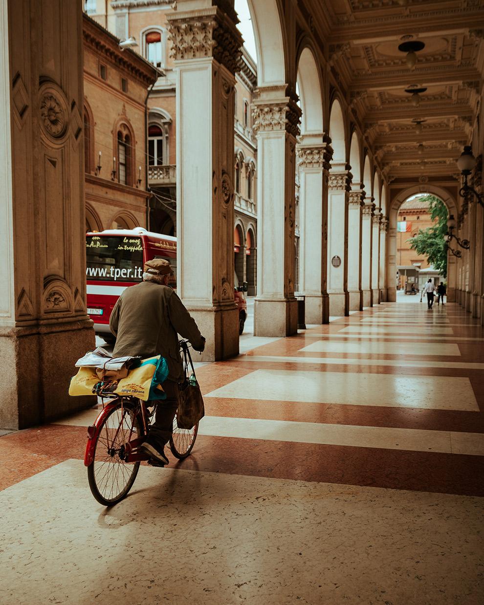 Man fiets door galerij met zuilen in Bologna