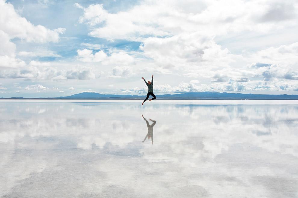 Weerspiegeling van sprong boven het zoute water van de Salar de Uyuni,