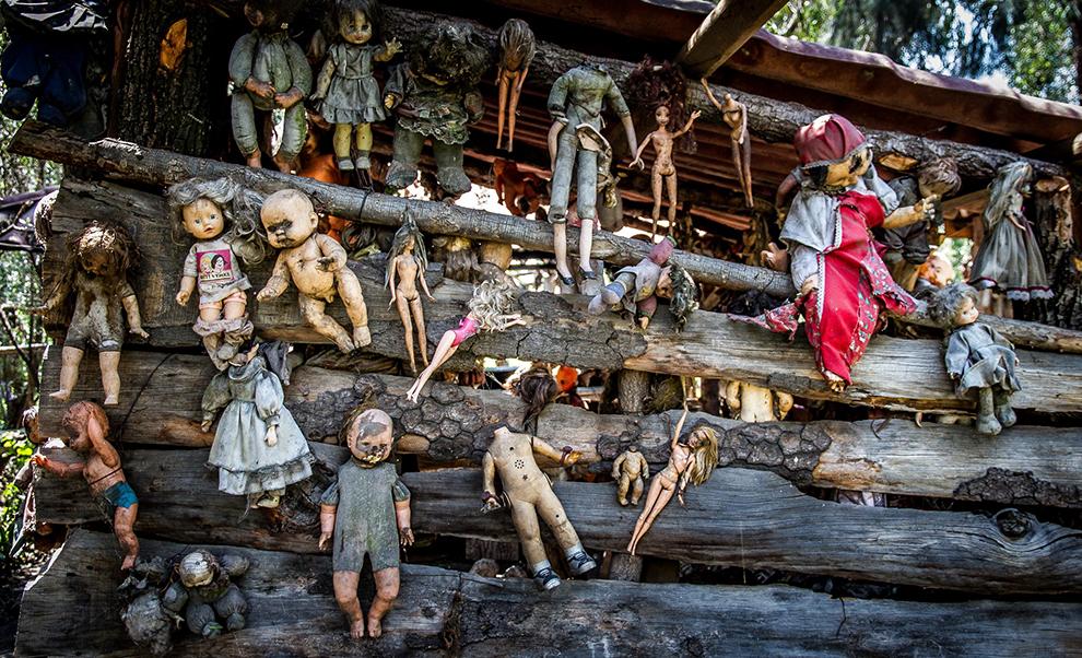 Enge verzameling van oude poppen aan houten muur