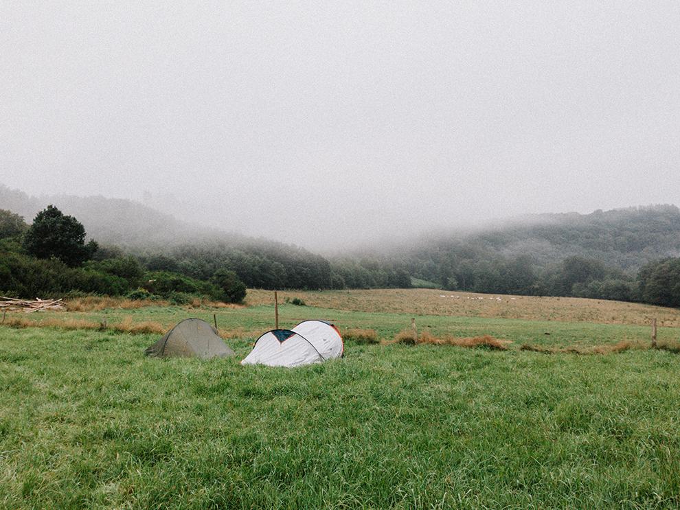 Tent midden op heuvel tussen de ochtend mist in de Belgische Ardennen