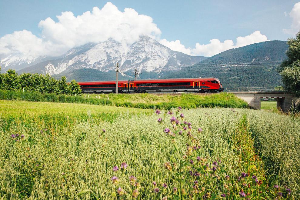 Rode trein raast door Oostenrijks landschap