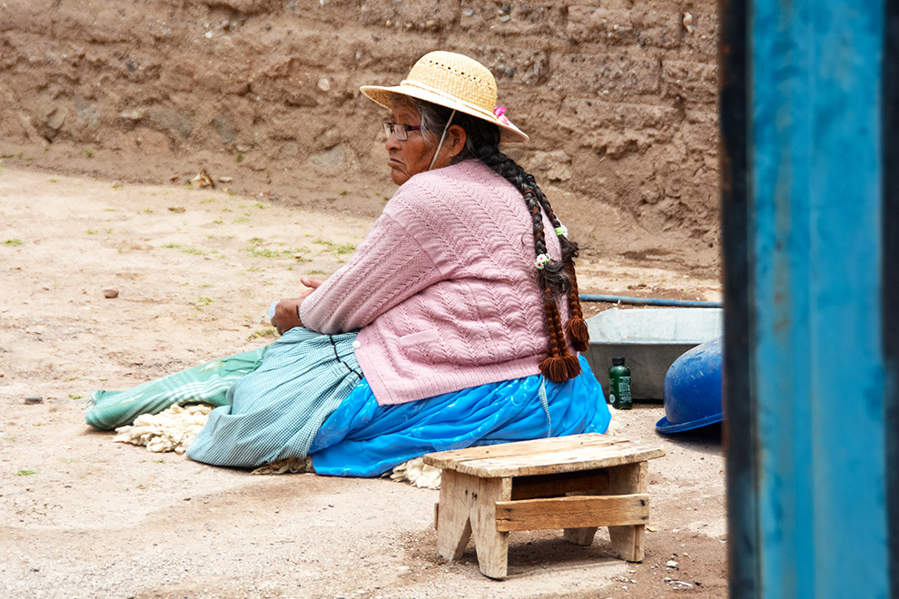 Bolivaanse vrouw zittend in het zand in traditionele kledij