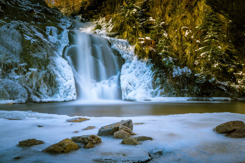 De waterval van de Bayehon bedekt met sneeuw