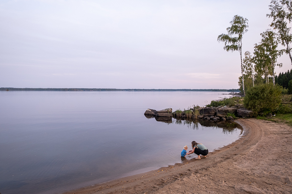 Samen met dochter Maeve zittend bij het water terwijl de lucht en het water paars kleurt in Zweden