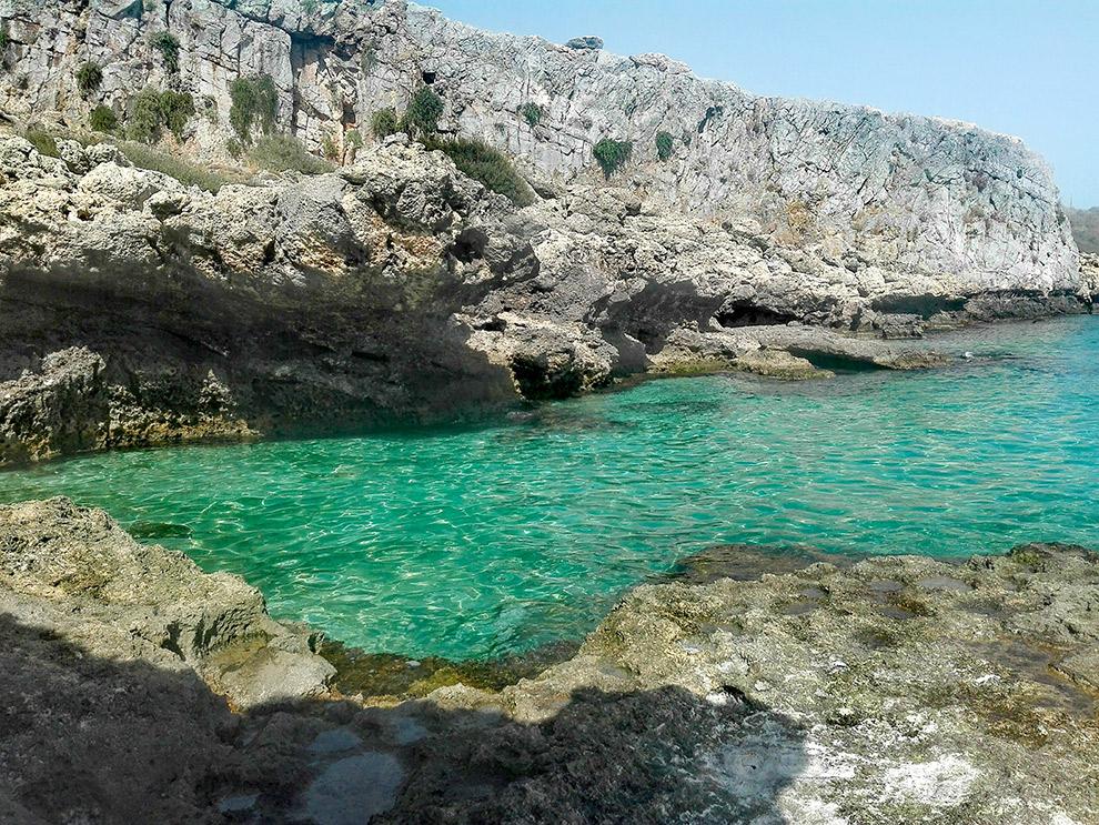 Steile rotsen bij helderblauw water in Griekenland