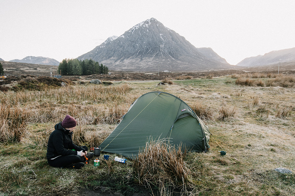 Koken op een gaspit midden in de natuur bij een tent