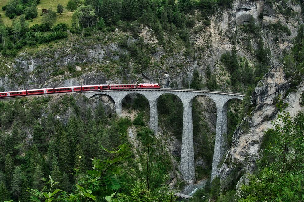 Rode Glacier Express rijdt over spectaculaire brug in het groene landschap