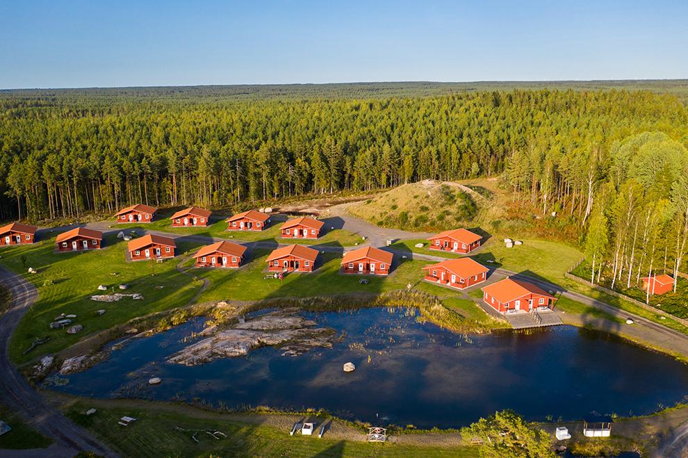 Dronefoto met in beeld de typisch rode Zweedse vakantiehuisjes