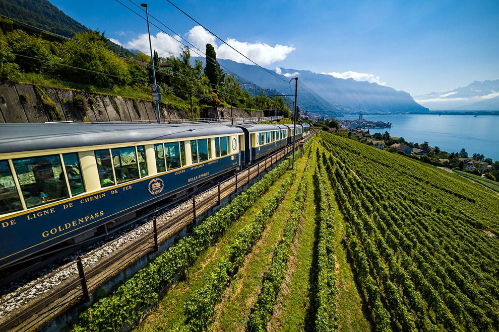 Comfortabele 20e-eeuwse Goldenpass trein reist door indrukwekkend Zwitserland
