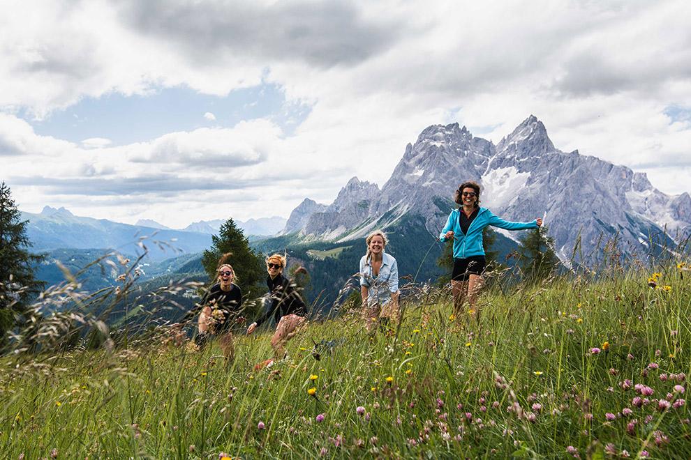 Groepsfoto in het gras met op de achtergrond de Italiaanse Dolomieten