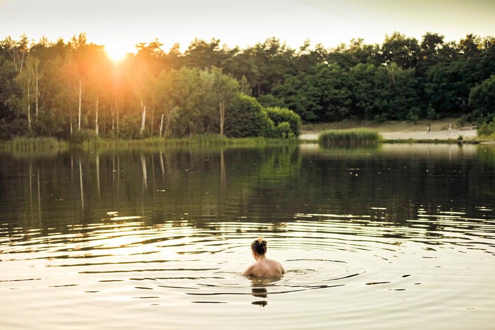 Zwemmen in een meer tijdens zonsopkomst