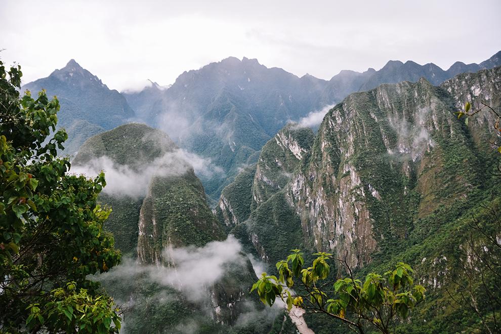 Mist hangt over de groene valleien bij het betreden van wereldwonder Machu Picchu
