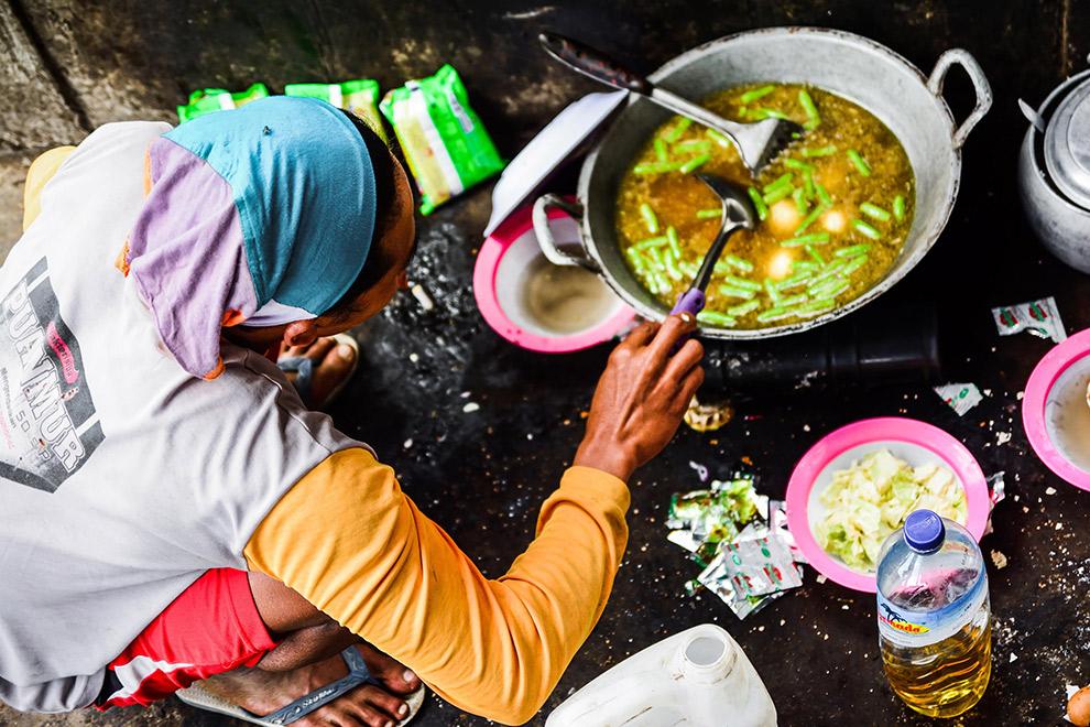 Indonesische vrouw maakt gele curry klaar voor lunch