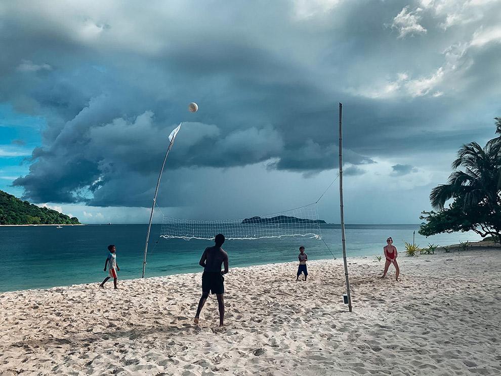Volleyballen op het strand van onbewoond eiland met donkere lucht op de achtergrond