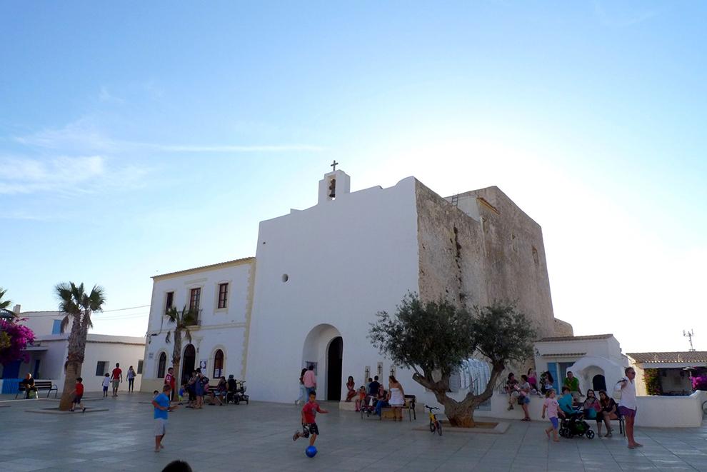 Sun appears behind a white little church in Formentera