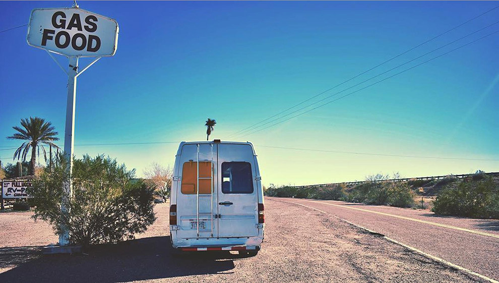 Camparbus geparkeerd langs de weg in typisch Amerikaans landschap