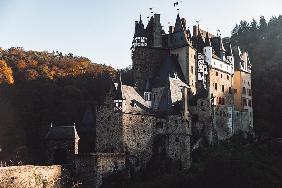 Fotogeniek kasteel omringd door beboste heuvels en een opkomende zon