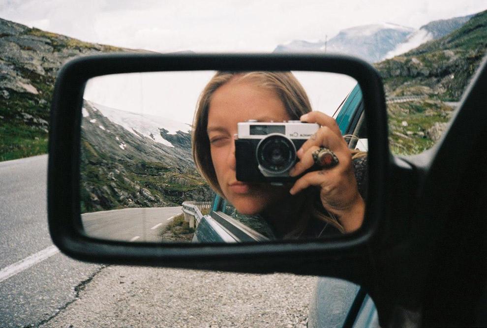 Analoge camera reflecteert in autospiegel