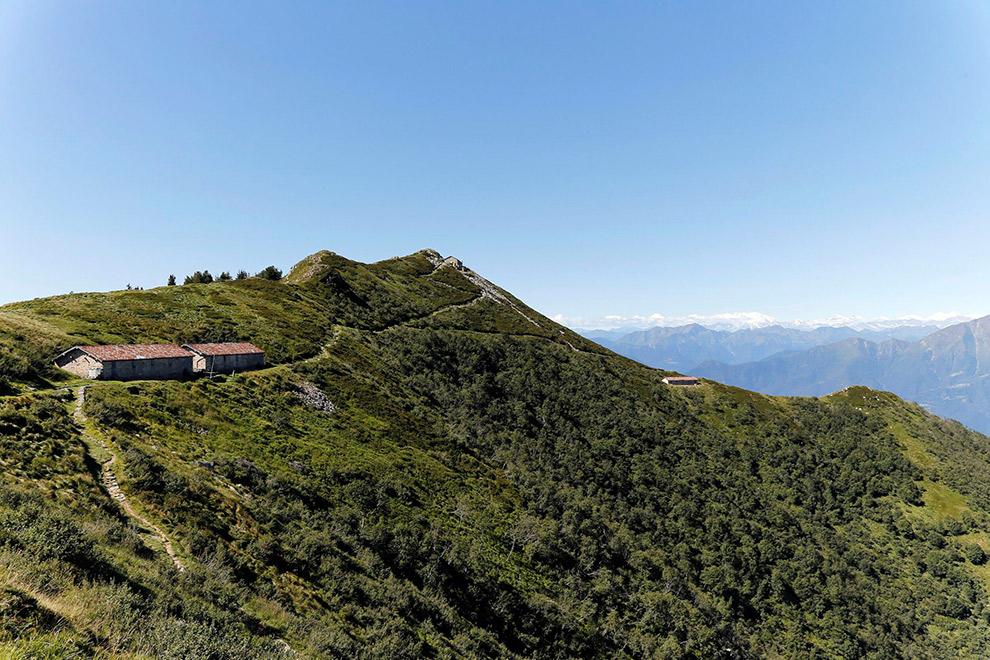 Alpe Cedullo boerderij bovenop berg in de verte